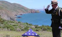NPS Officer salutes a US flag.