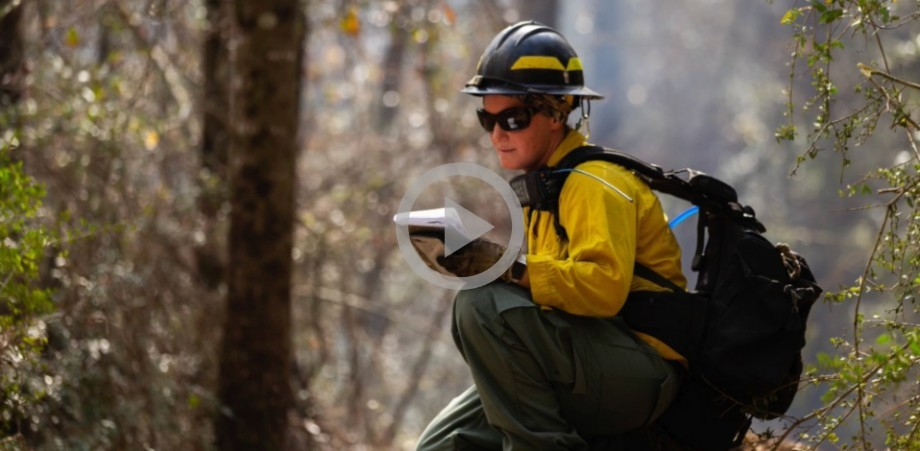 A woman in a yellow shirt, hard hat and firefighting gear kneels on the ground in a forest and talks on a radio.