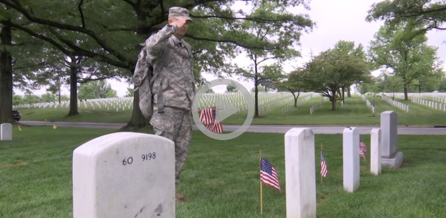 A male soldier stops to salute a grave in a cemetery while placing American flags.