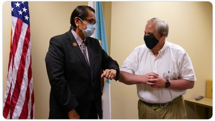 Secretary Bernhardt wears a mask and bumps elbows with a man in a suit while standing in a conference room.