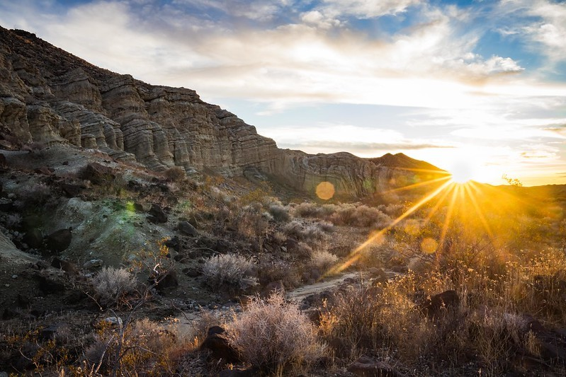 Desert landscapes with mountain and sun shining.