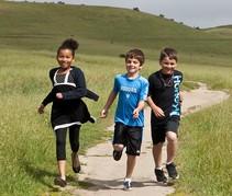 Three children running on a trail.