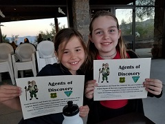 Two girls holding agents of discovery certificates of completion.