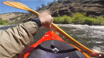 Video still of a kayaker in a river.