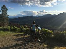 A biker looking towards a mountain range.