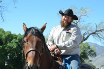 A man wearing a black cowboy hat on a back of a horse smiles.