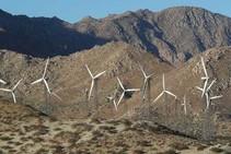 wind turbine on a desert mountain ridge.