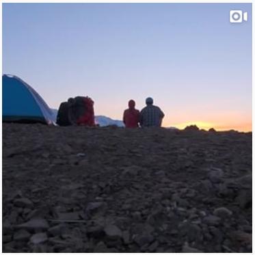 Video still of camper watching a sunset.
