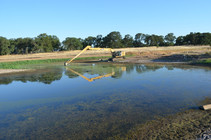 Heavy equipment cleaning a pond.