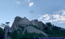 Military jet planes performing a flyover above Mount Rushmore.