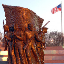 Civil war bronze monument with American flag in background.