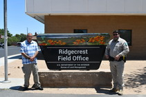 Two men standing next to the Ridgecrest Field Office sign