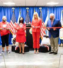 People cutting a red ribbon at a ceremony.