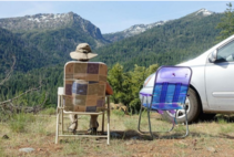 Person sitting in folding chair looking out into a valley.