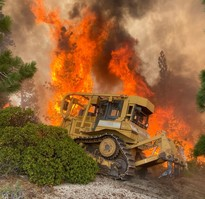 A fire dozer in front of a raging fire clearing a fireline.
