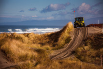 Off road vehicle on sand dunes by the beach.