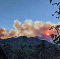 Smoke covered sun over a mountain.