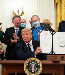 President Trump holding up the Act he signed.