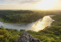 View looking out over a high river bend at sunset.