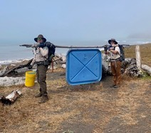 Two people carrying trash from the seashore by using a large stick.