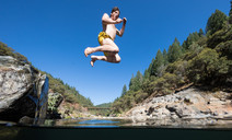Man jumping into a swimming hole.