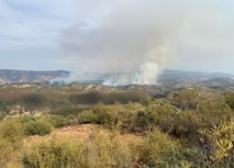 Smoke billowing from distant hillsides.