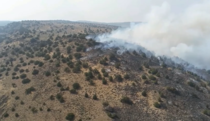 View of fire burning a hillside from above.
