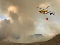 Helicopter flying over a smoke filled landscape.