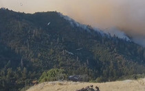 View of a mountaintop with smoke in the background.
