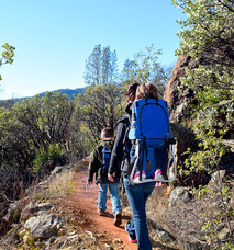 Family hiking up a trail.