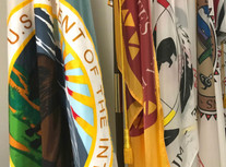 Close up of several flags against a wall.