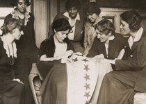 An old historical photo of women sewing a flag.