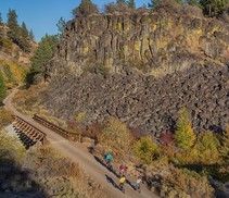 Bicyclists traveling on a trail after crossing a bridge below a rock formation.