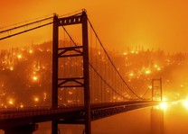 Fire glowing on a hillside with the silhouette of a suspension bridge in the foreground.