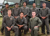 Eight marines posing for a photo in front of a large fire vehicle.