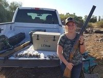 Woman holding a shotgun sitting on the tailgate of a truck with hunting gear in the bed.