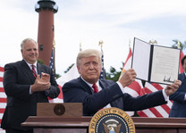 President Trump holding a signed bill.