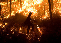 Silhouette of firefighter in front of a fire.