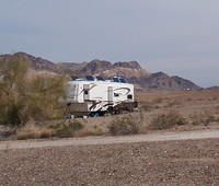 A desert with RV's parked.
