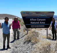 Three women standing next to the Afton Canyon Natural Area sign in a desert.
