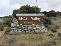 A dirt road with powerlines overhead next to a sign for McCain Valley.