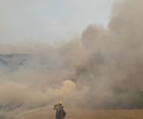 Firefighter spraying water on a smoke filled field.