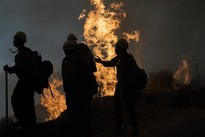 Silhouette of firefighters in front of a fire.