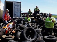 Several people standing in or next to a pile of tires behind a parked semi truck.