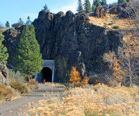An opening of a railroad tunnel with a trail leading up to it.