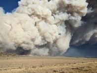 An aircraft flying above a field with a huge smoke plume behind it all.