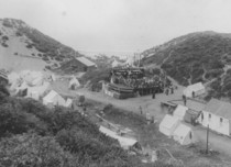 Old black and white photo of a seaside camp.