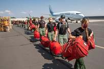 Firefighters holding their red bags walking on a flightline with masks on.