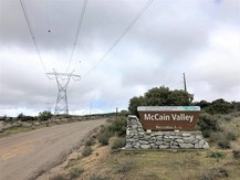 Dirt road with powerlines overhead, next to the McCain Valley sign.