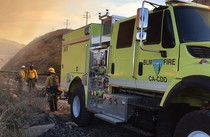 BLM fire engine parked in some gravel with three firefighters standing nearby.